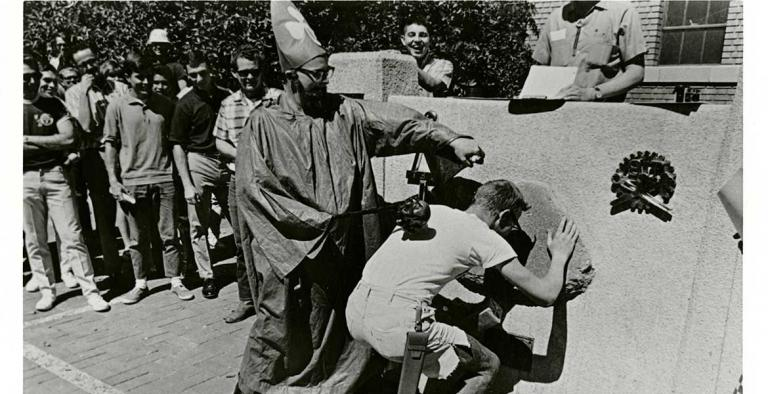 A man wearing a robe and a hat with a three-leaf clover on it whacks another young man on the back while the second man leans down to kiss a stone embedded in a concrete slab.