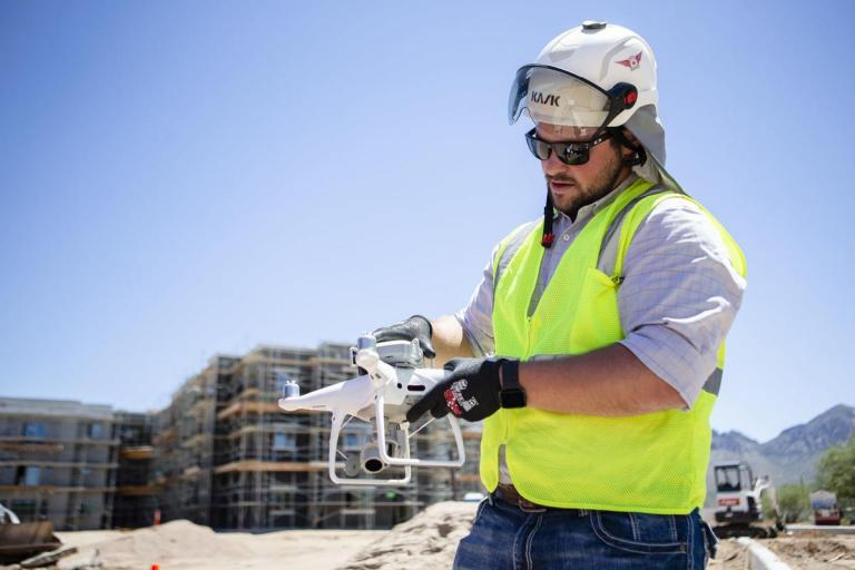 A man in a yellow construction vest and hardhat holds a drone.