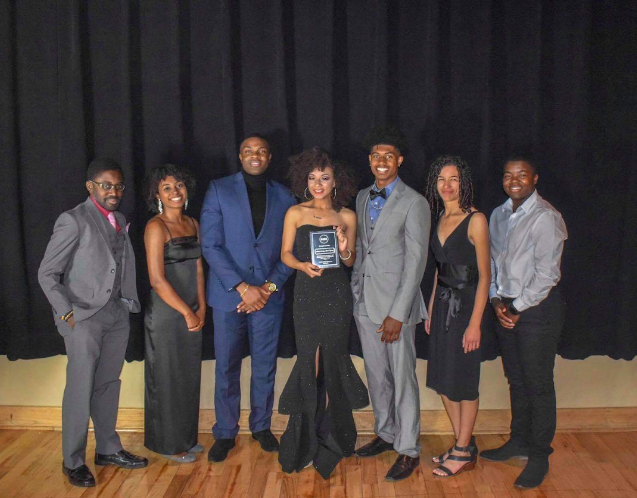 A group of seven black students in formal clothing smile for a photo. The woman in the center holds a plaque.