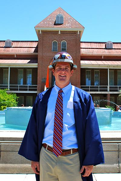 Jeff Tysoe in hardhat and gown in front of the Old Main fountain