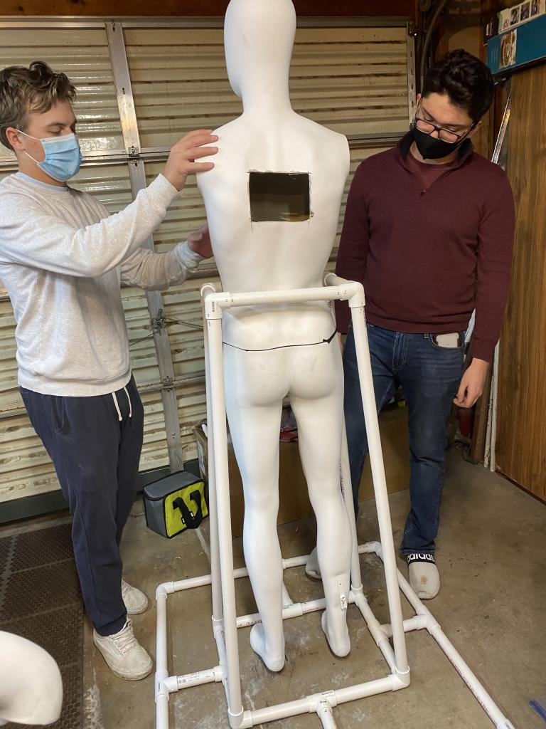 Two students wearing face masks attach arms to a white mannequin, which has a hole carved in its back and is held upright by a PVC pipe base.