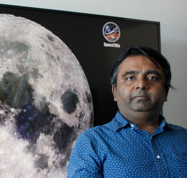 Jekan Thanga, standing in front of a TV screen with a giant image of the moon on it.