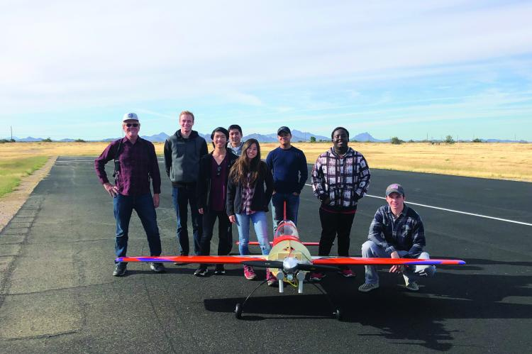 A group of eight people stand smiling for a photo with a hand-built airplane, which sits in front of them and looks to have a wingspan of about 10 feet.