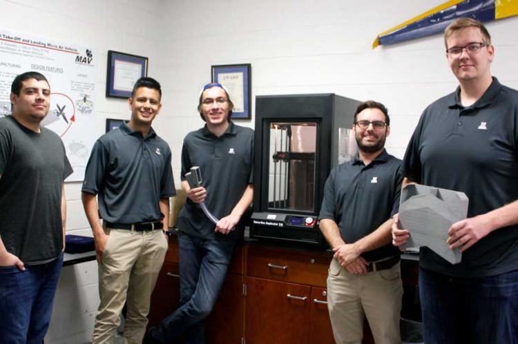 Five students standing by a 3D printer