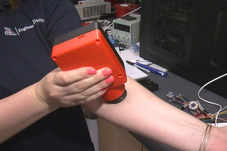 Close up of a woman holding a plastic device onto her left arm.