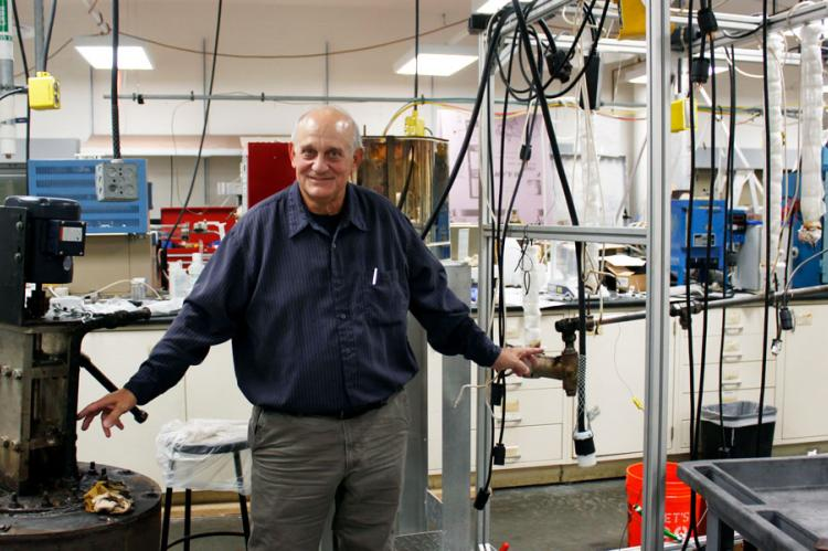 Don Gervasio, wearing a long-sleeved blue shirt, stands between a pump and pipe in a laboratory with tubes hanging in the background