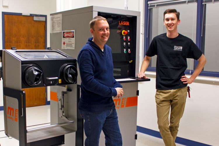 "Two young men standing next to a machine about the same height as them, with a screen and a series of buttons. It says ""LASER"" at the top."