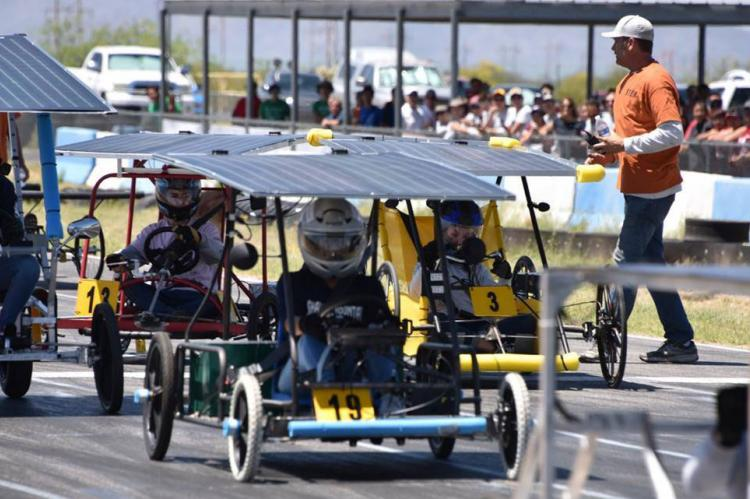 Students in solar-powered go-karts get ready at the starting line of a race.