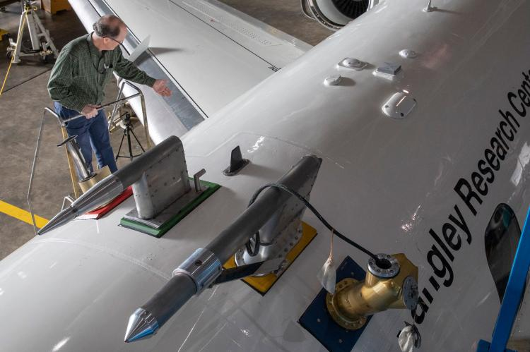 """A photo shot from above of a man at the top of a ladder next to a large white airplane, which says """"Langley Research Center"""" on the side."""