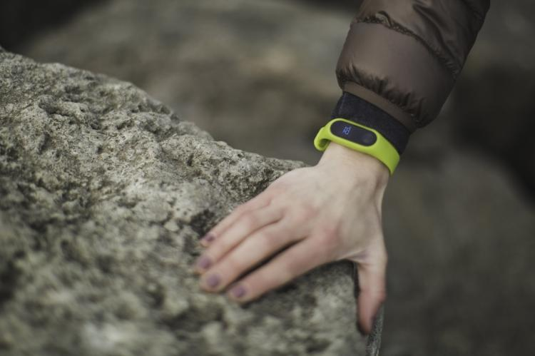 A close-up of a hand resting on a rock. There is a green smartwatch on the wrist.