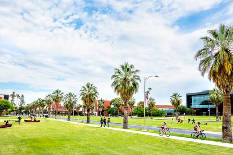 A shot of the UA Mall on a sunny day. Students are riding bikes and walking in the sunshine.