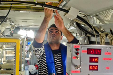 Doctoral student Hossein Dadashazar collects cloud water samples aboard the Navy Twin Otter.
