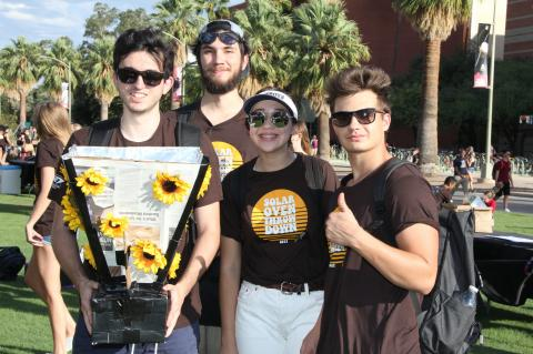 Four students gather around their solar oven, which is made of cardboard and foil and decorated with plastic sunflowers