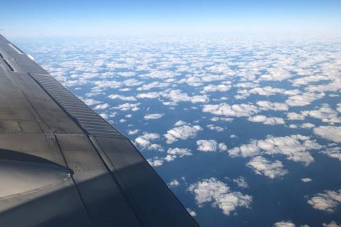 photo taken from a plane showing cumulus clouds from above. The wing of the plane is visible in the left of the frame