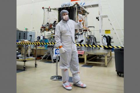 Bradley Williams in a white safety suit in front of a spacecraft.