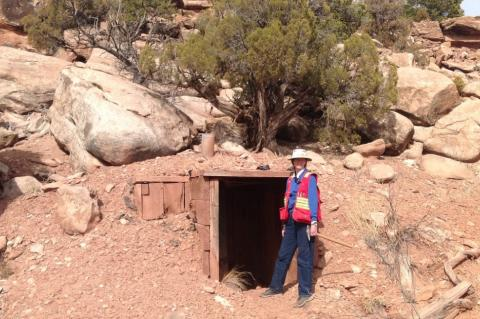 Isabel Barton wearing a red vest and standing next to the entrance of a mine in a desert setting.