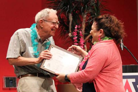 William Cosart, wearing a blue lei, hands a framed certificate to Claudia Arias.