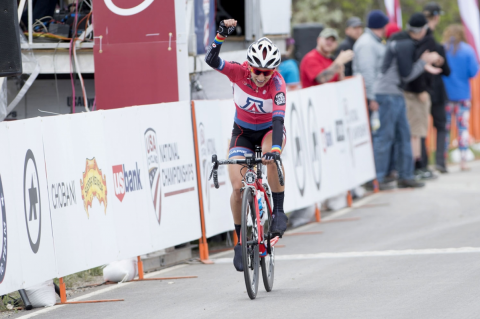 Erica Clevenger, on her bicycle wearing a UA jersey, raises her fist above her head in victory