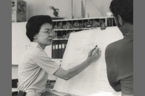 Frances Walker explaining a blueprint on a large white sheet of paper to an onlooker.
