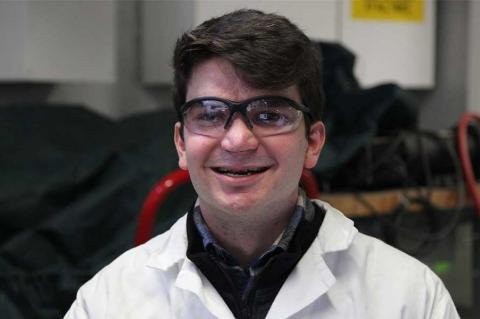 Gabriel Schirn wearing protective eye gear and a lab coat