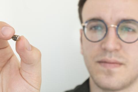 A man holds up a tiny electronic device, about the size of a chocolate chip.