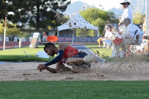Mo Almarhoun sliding in the dirt after completing a long jump.