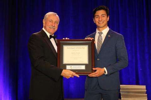 """Roberto Peralta stands on a stage accepting a framed certificate from an older man. The certificate says """"Astronaut Scholarship."""" The men are in formal wear and there is a blue curtain behind them."""