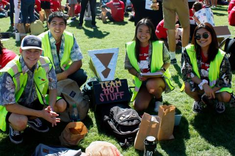 "Two young men and two young women wearing Hawaiian shirts and bright yellow vests kneel for a photo next to their solar oven, a cardboard and aluminum foil device labeled with their group name: ""Team Hot Stuff."""
