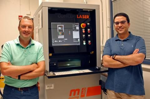 Andrew Wessman and Mohammed Shafae standing next to a 3D printer, which is about two feet wide and a bit taller than them.