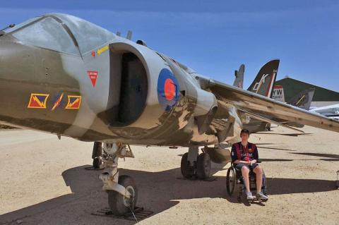Alex Spartz, an engineering student and wheelchair user, sits in front of an airplane at the Pima Air and Space Museum.
