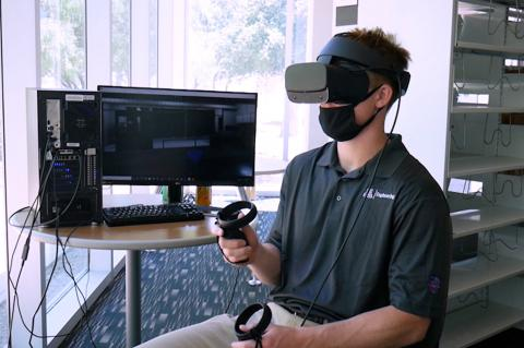 A student sitting next to a computer monitor and wearing a VR headset.