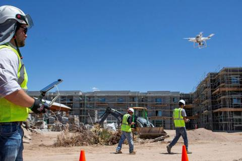 A man in a yellow construction vest and hard hat operates a drone on a construction site.