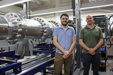 Alex Craig and Jesse Little standing next to a hypersonic wind tunnel, a horizontal metal tube about the circumference of a large tree.