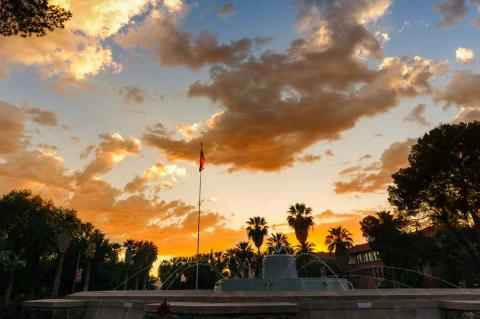 The sun sets over a fountain on the UA campus.