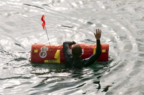 A swimmer in a wet suit holds onto an EMILY robotic rescue buoy