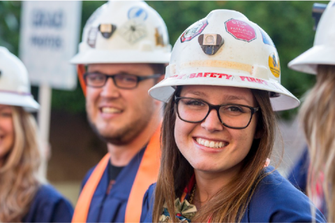A student smiling and wearing graduation garb and a white hard hat covered in stickers. There are three other students in the frame, wearing the same combination, but out of focus.