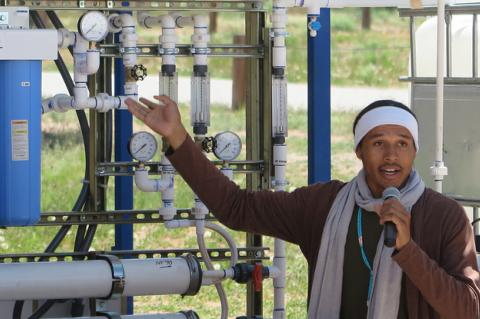 A young man holding a microphone gestures toward a systems of pipes and gauges.