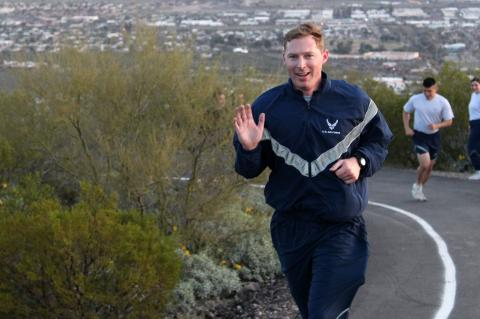 Ryan Raettig smiling and waving as he runs up Tumamoc Hill.