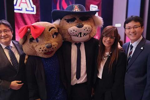 Two men and a woman pose for a photo with Wilma and Wilbur Wildcat