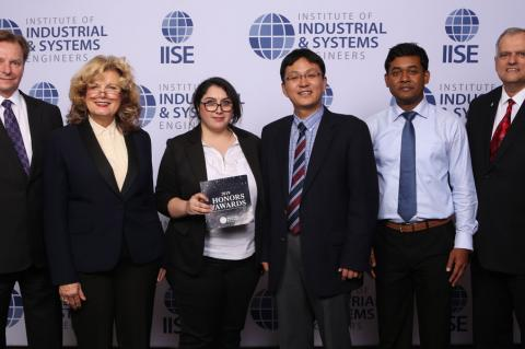 Six professionals pose for a photo in front of an IISE backdrop.