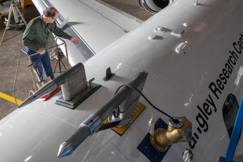 "A photo shot from above of a man at the top of a ladder next to a large white airplane, which says ""Langley Research Center"" on the side."