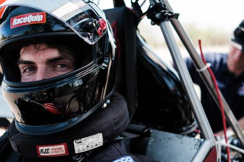 A close up photo of a student wearing a dark motorcycle helmet and sitting in a Formula-style vehicle. A man is behind him working on the vehicle.