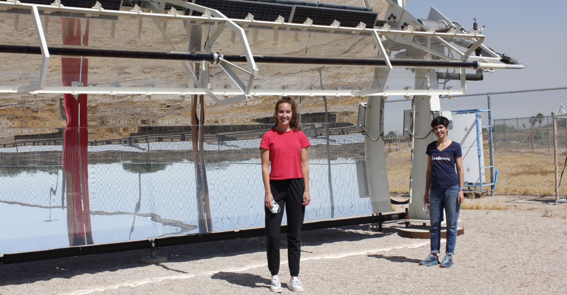 Two women stand in front of a solar-powered desalination system, shaped like a giant curved mirror
