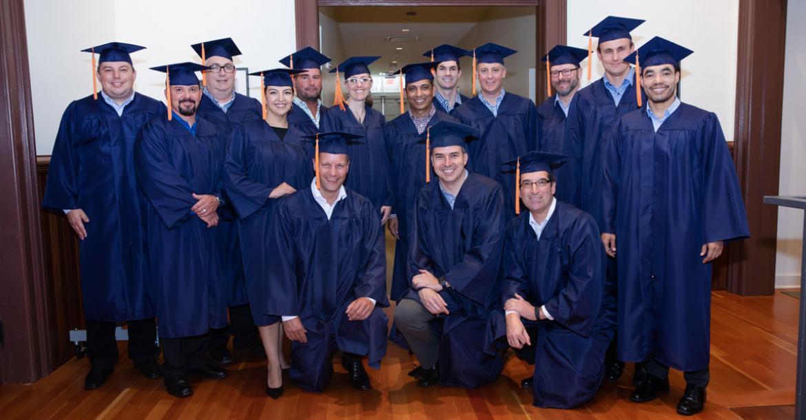 A group of 15 men and women wearing blue graduation caps and gowns