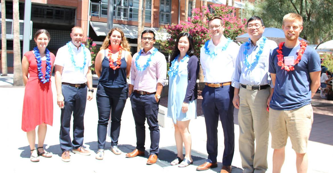 Eight faculty members smiling and wearing red and blue leis.
