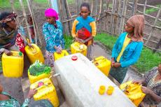 Mari Tuji, with purple headscarf, and her neighbors collect water from one of 10 water-dispensing stations in Kelecho Gerbi, Ethiopia, built by Water1st and a local organization. (Photo courtesy of Water1st International)