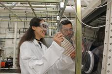 Two students wearing lab coats and goggles in a lab.
