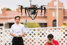 A student in a white polo shirt flies a tethered drone outside Old Main at Engineering Design Day