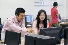 Ming Li leans over a computer, smiling and helping a student.