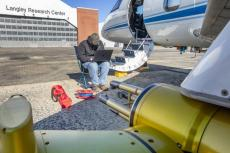"""A man sits on a folding chair using a laptop, next to the steps of an airplane. The building behind him has a sign that says, """"Langley Research Center."""""""